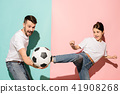 The young football fans plaing with ball on blue and pink trendy colors. 41908268