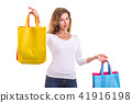 Beautiful caucasian woman wear white shirt and jeans and holding colorful shopping bags. Studio shot isolated on white 41916198