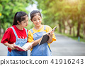 Pretty asian twins girl or students reading a book in the public park 41916243