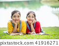 Pretty asian twins girl or students reading a book in the public park 41916271