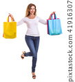 Beautiful caucasian woman wear white shirt and jeans and holding colorful shopping bags. Studio shot isolated on white 41916307