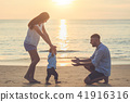 Family on the beach, Mother holding hand of her son and walking, playing on the beach with her husband 41916316