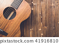 New brown guitar on wooden board 41916810