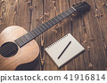 New brown guitar on wooden board 41916814