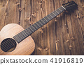New brown guitar on wooden board 41916819