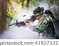 Squad of soldiers patrolling across deep forest. 41927132