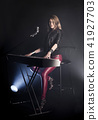Blonde girl musician pianist plays perform on white digital piano, sits on chair, sings into retro 41927703