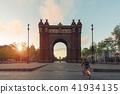 Tourist riding bicycle near Bacelona Arc de Triomf 41934135