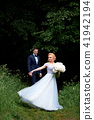 The bride is spinning, in a blue beautiful dress. The groom stands at a distance and admires.Park or 41942194
