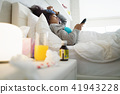 Black Woman With Flu And Cold Watching Tv At Home 41943228