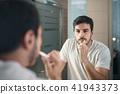 Hispanic Man Brushing Teeth In Bathroom At Morning 41943373