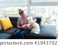 Dog Owner Cleaning Paws To Little Pet At Home 41943702