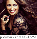 beauty smiling rich woman in lace with dark red lipstick, flying hair close up 41947251