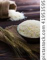 White rice and ear of paddy on wooden table. 41953595