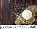 White rice in bowl and ear of paddy on wood table. 41953600