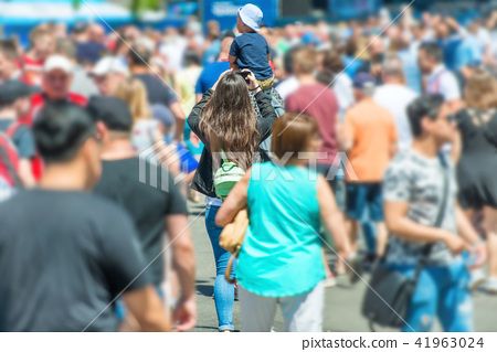 Woman with smartphone and child in crowd 41963024