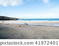 바위와 언덕에 둘러싸인 얕은 모래 해안과 모래에서 노는 사람들 영국 교외에서 41972401