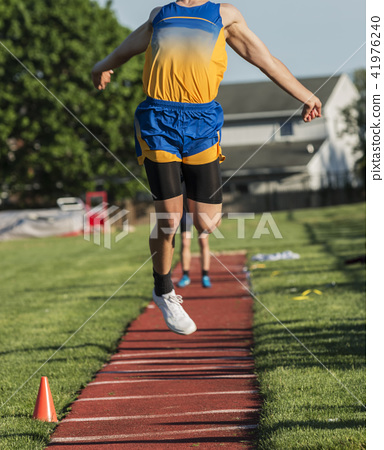 High school boy triple jumping during competition 41976240