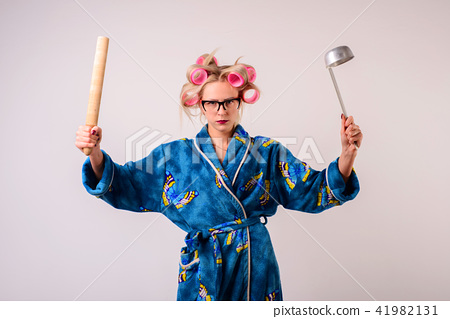 Serious housewife with a ladle and battledore 41982131