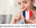 Young woman with gingerbread heart cookies with flag 41982749
