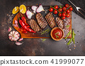 Grilled beef steaks with spices on wooden board 41999077