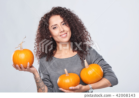 Smiling woman holding ripe pumpkins 42008143