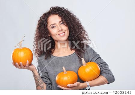 Smiling woman holding ripe pumpkins 42008143