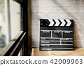 movie clapper on wood desk with windows light. 42009963