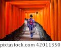 Woman in traditional kimono walking at torii gates 42011350