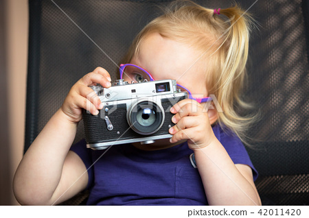 Little girl making photo with vintage camera 42011420
