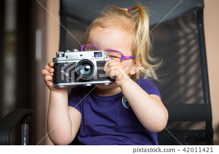 Little girl making photo with vintage camera 42011421