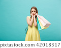 Portrait of beautiful serious young woman with shopping bag over blue studio background. 42018317