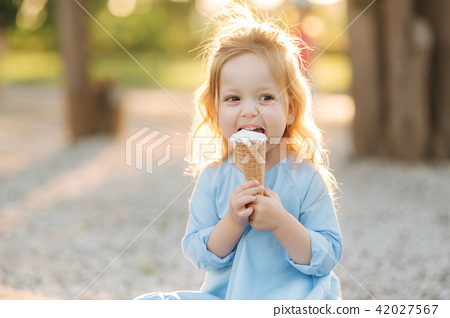 Beautiful little girl in a blue dress eating an ice cream 42027567