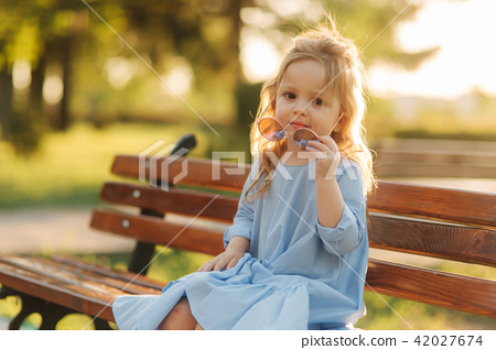 Little girl model in blue dress and sun glasses sits on a bench in the park 42027674
