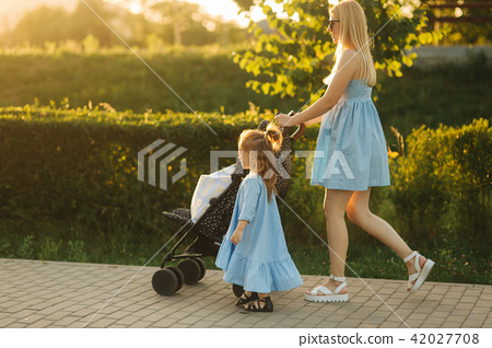 little daughter helps mom push the baby carriage. Happy family 42027708