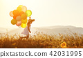 happy child with balloons at sunset in summer 42031995