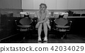 Black and white photo of young girl sit in armchair with washbasin in salon 42034029