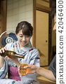 A woman in a yukata pouring beer at the edge 42046400