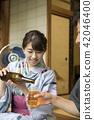 툇마루에서 맥주를 따르는 유카타 차림의 여성 42046400