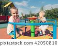 Image of joyful siblings having fun on carousel 42050810