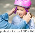 Mother is helping her daughter with safety helmet 42059161