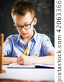 Boy solving math problems at home 42063366