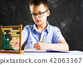 Boy solving math problems at home 42063367