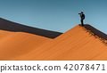 Young male photographer standing on sand dune 42078471
