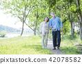 หญิงสาวอาวุโสเดินเล่นในสวนเขียวขจี 42078582