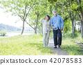 หญิงสาวอาวุโสเดินเล่นในสวนเขียวขจี 42078583