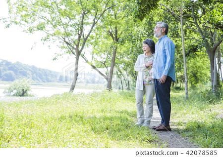 หญิงสาวอาวุโสเดินเล่นในสวนเขียวขจี 42078585