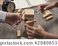 Hand of engineer point a blocks wood tower game. 42080653