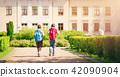 Children with rucksacks standing in the park near school 42090904