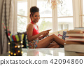 Young Woman Texting On Phone And Looking At Camera 42094860